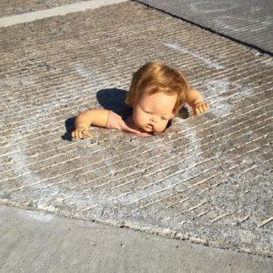 doll in crosswalk hole