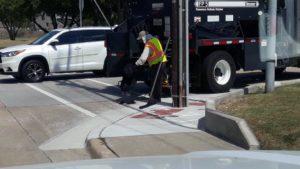 city worker fills hole in crosswalk