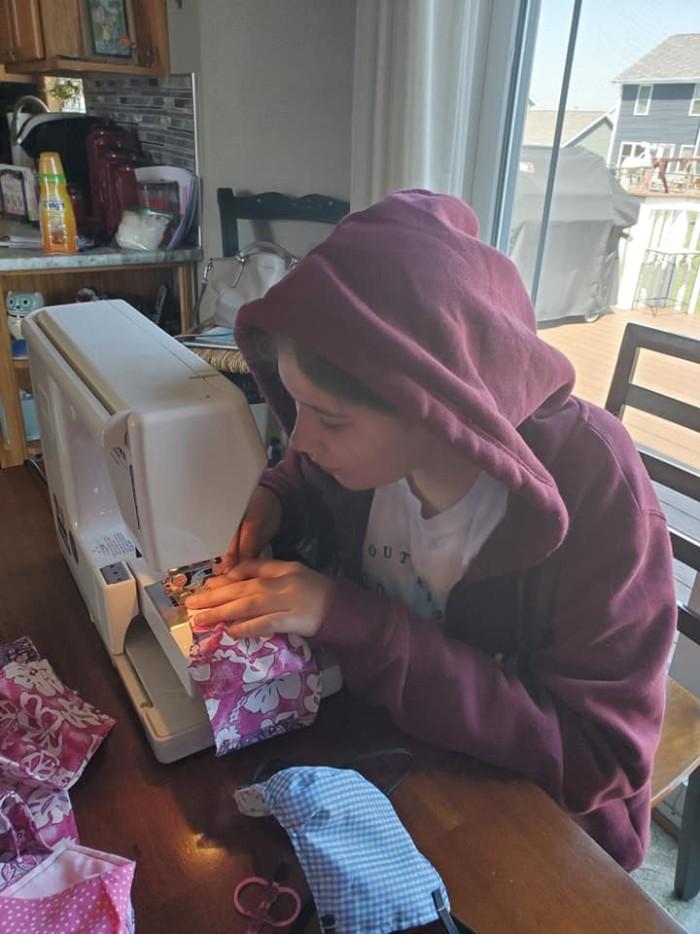 woman at sewing machine, sewing mask