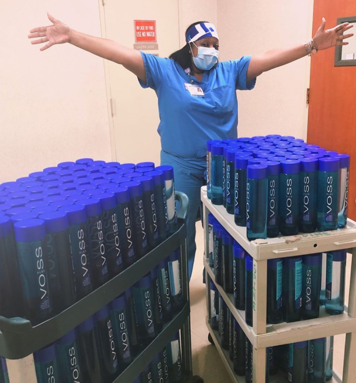 healthcare worker celebrating with two carts full of voss water