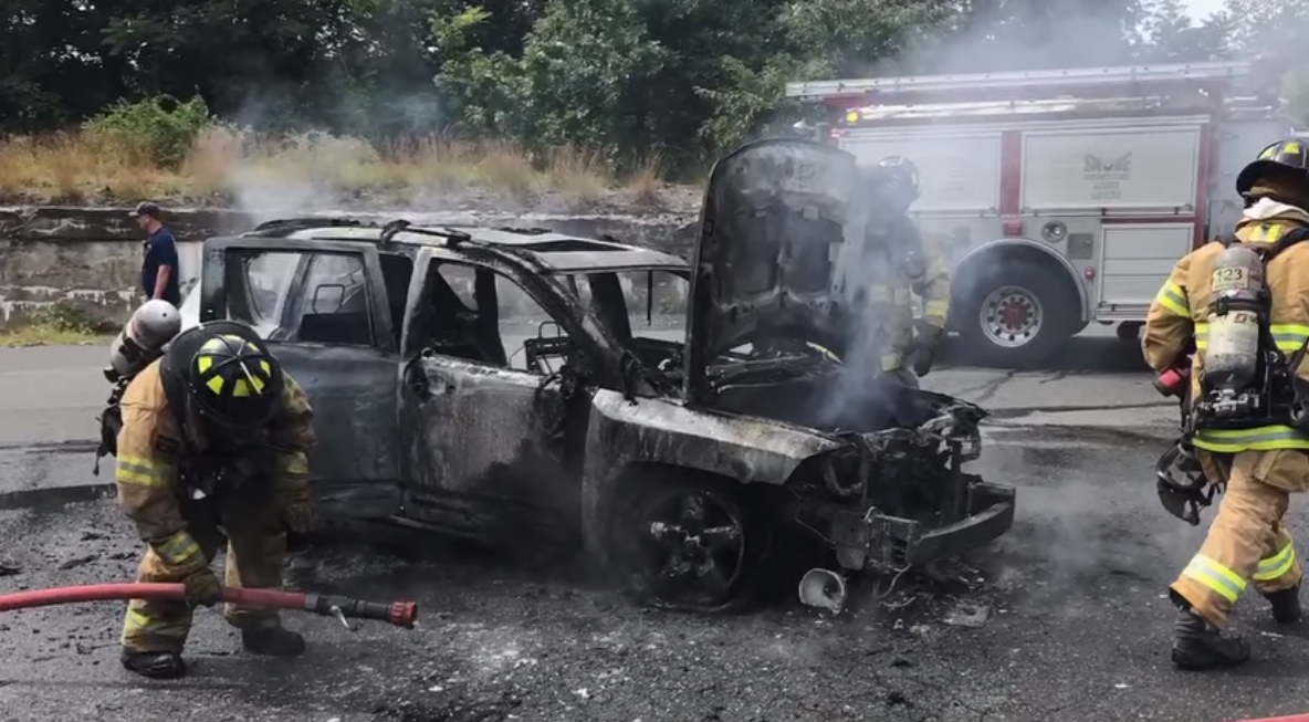 firefighters with burned car