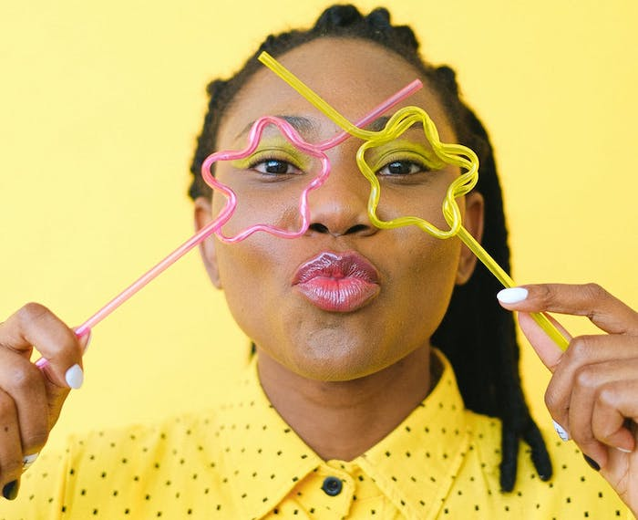 woman in yellow holding up crazy straws