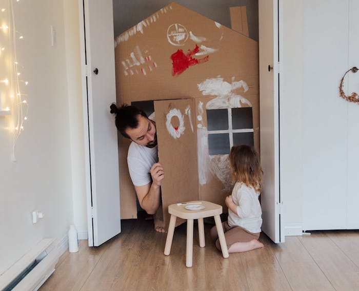 dad playing imagination in a cardboard house with his daughter