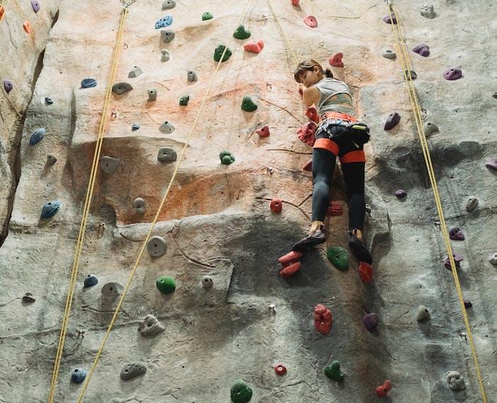 a woman indoor rock climbing