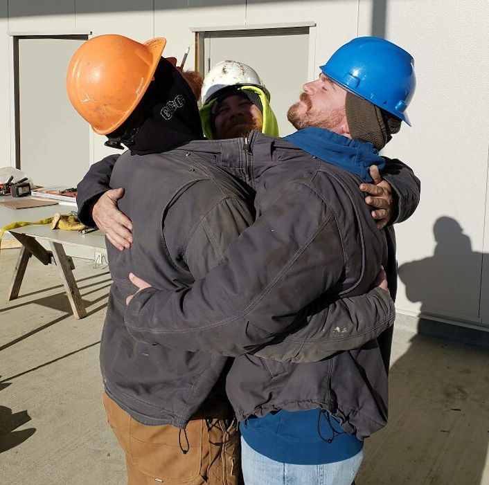 construction workers hugging