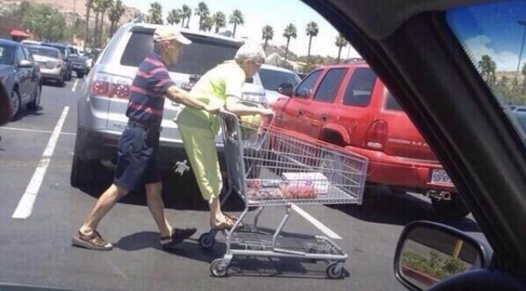 man pushing wife on grocery cart