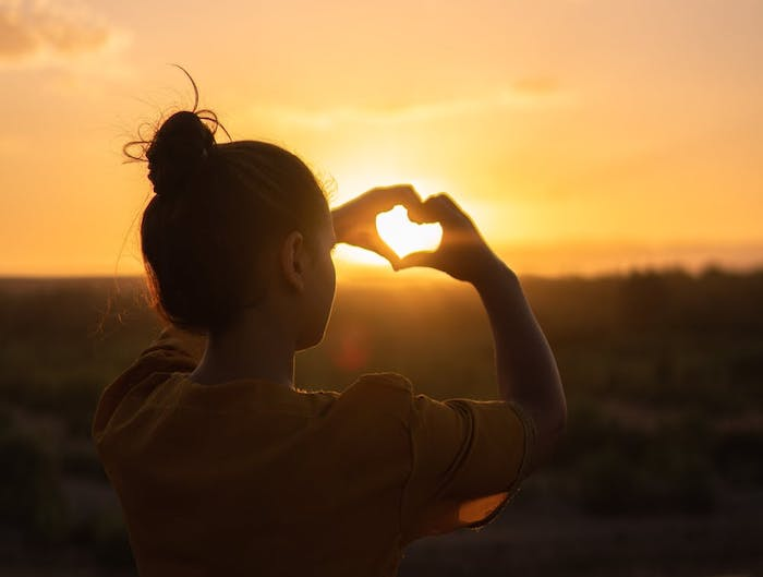 woman making sunset heart with hands