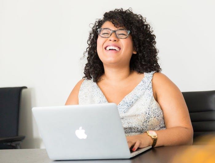 woman laughing at laptop