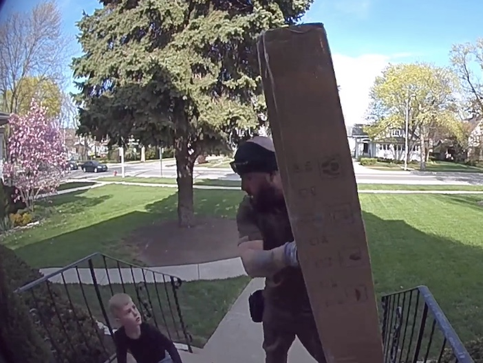 deliveryman lifting package off boy