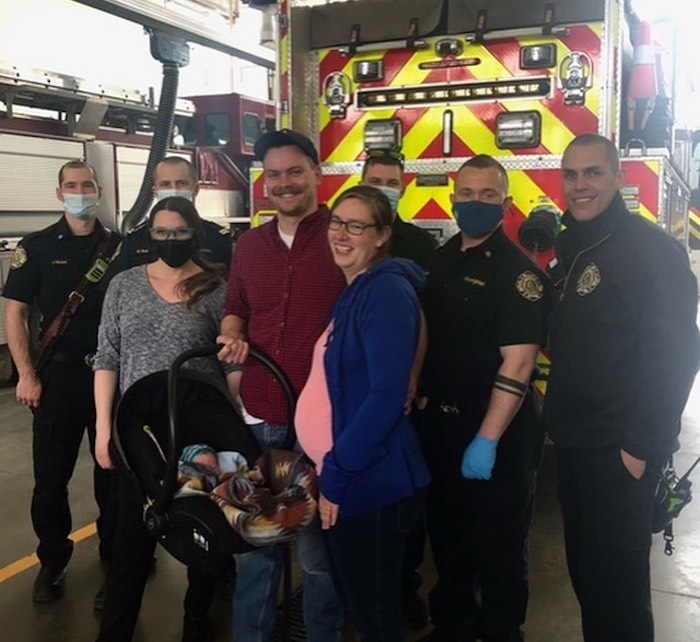 a family smiling with firefighters