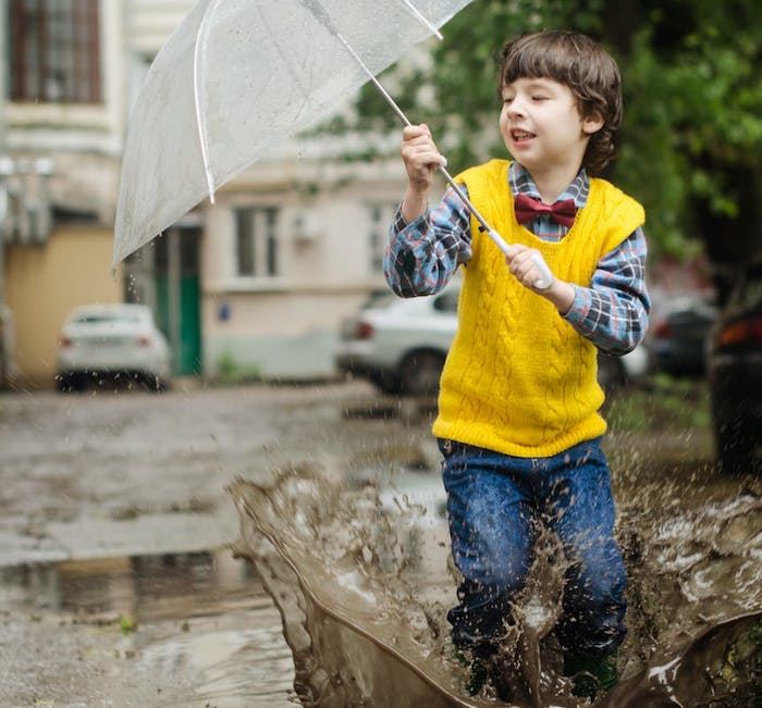 boy jumping in muddy puddles