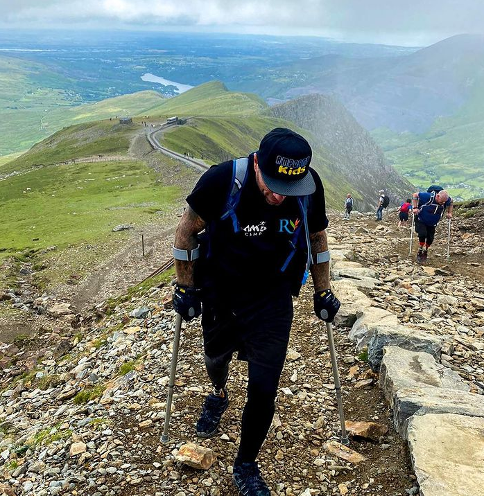man with prosthetic leg and crutches walks up mountain