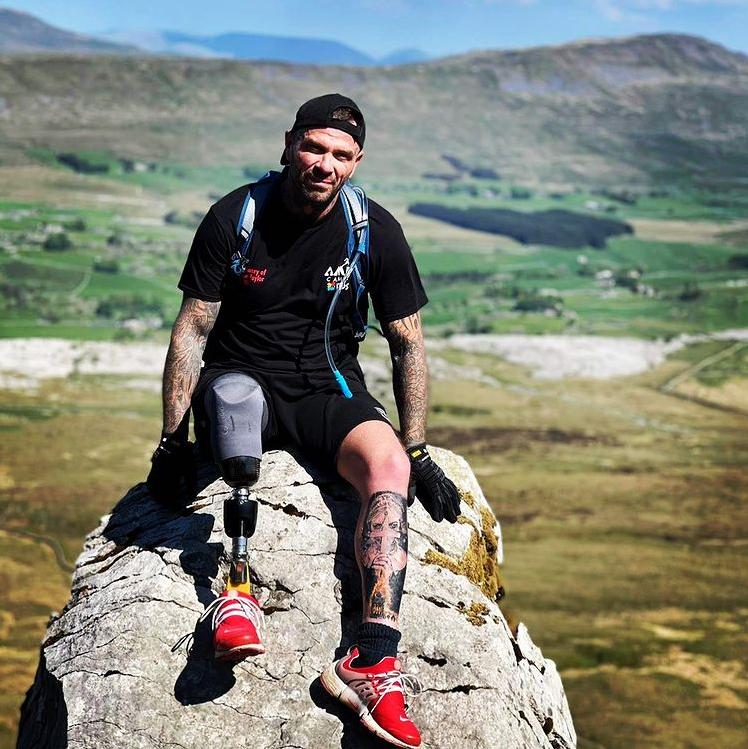 man with prosthetic leg sitting on giant rock