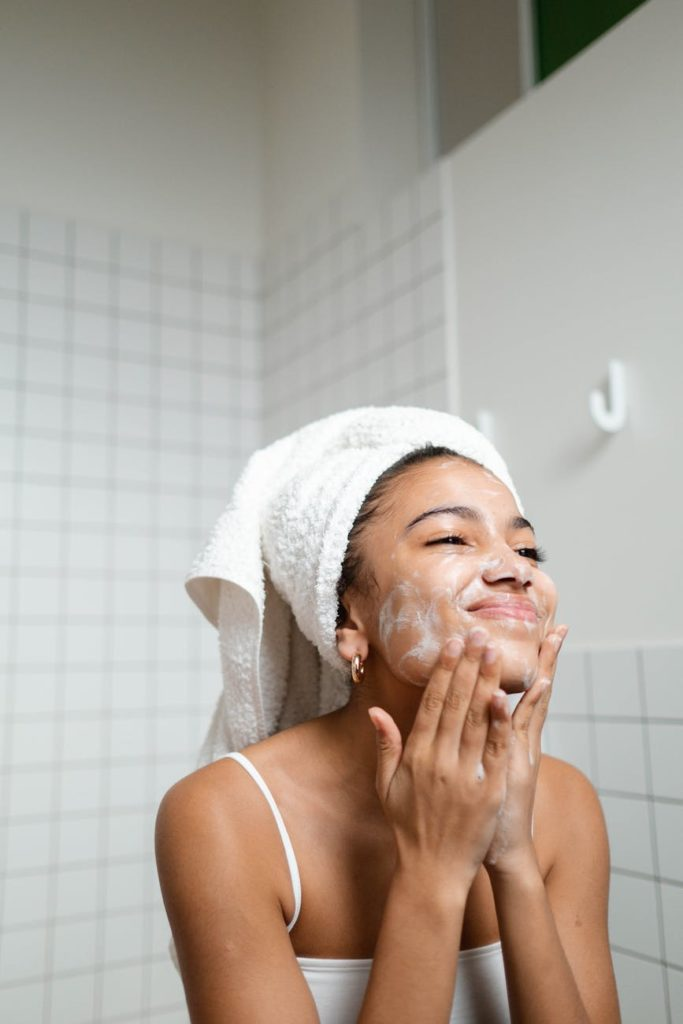 woman washing her face with hair in towel