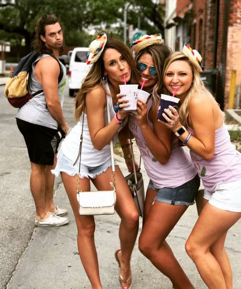 women posing with man in background copying them