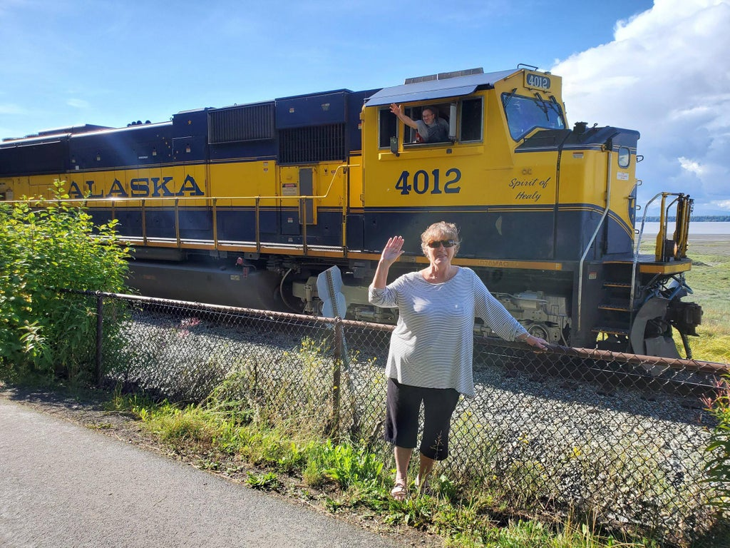 woman waving with train in background