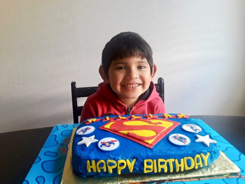 boy smiling with superman cake