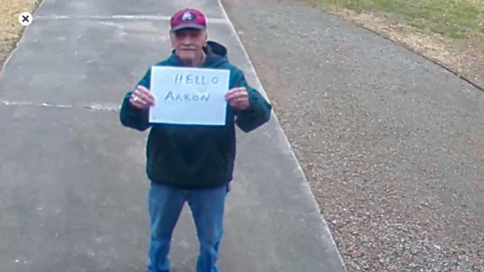 grandpa holding sign that says hello aaron