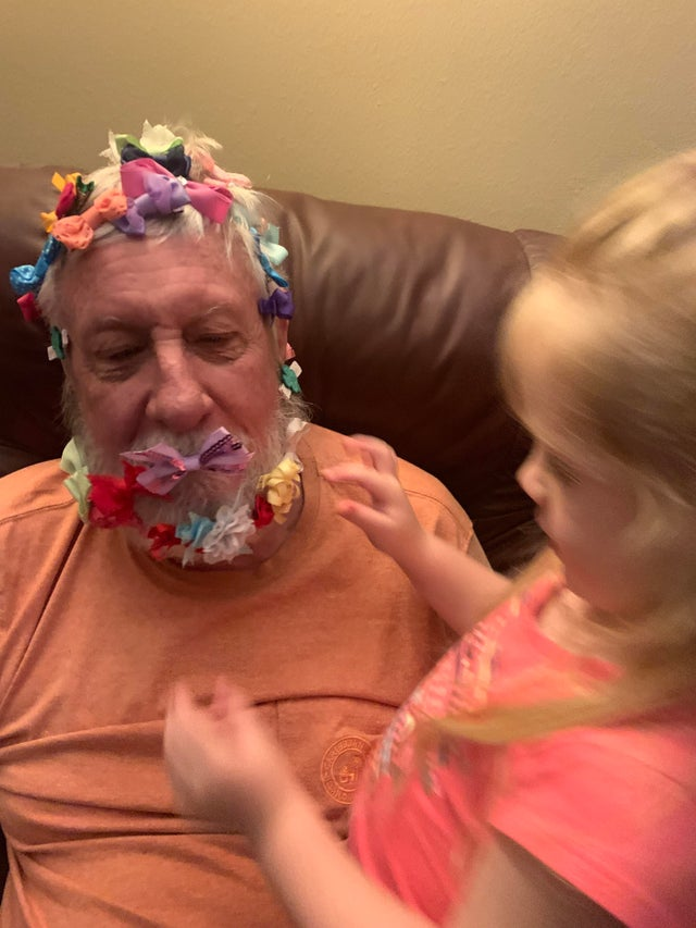 grandpa with a bunch of bows all over his head next to his granddaughter