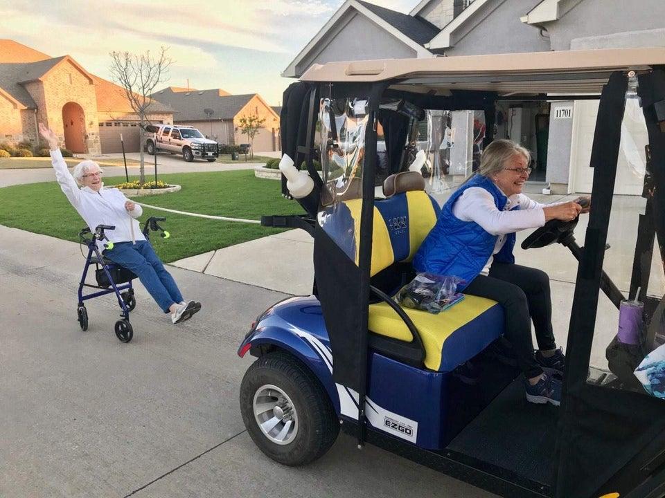 grandpa in golf cart pulling grandma sitting on walker