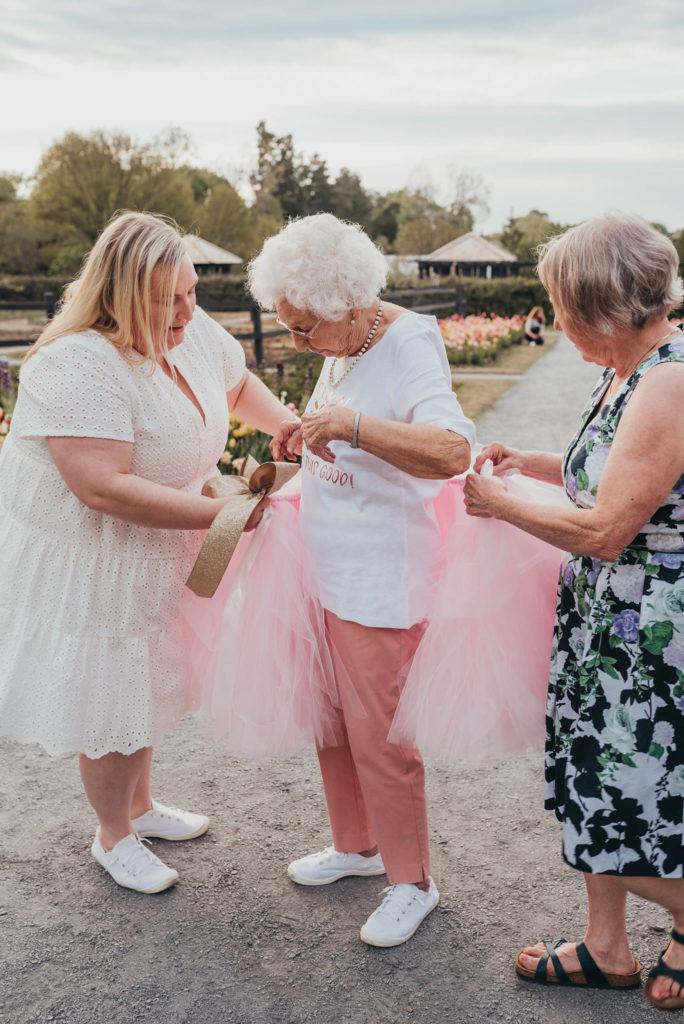 two woman helping grandma put on a tutu