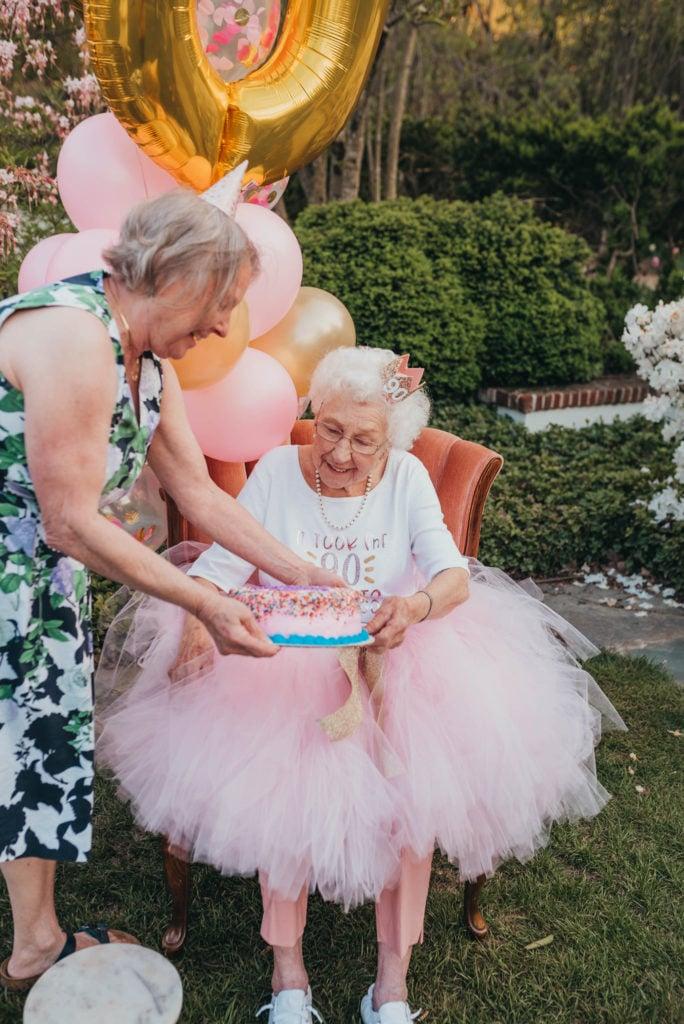 woman handing grandma a birthday cake