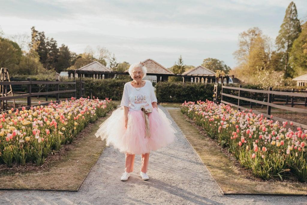 grandma in tutu posing around flowers