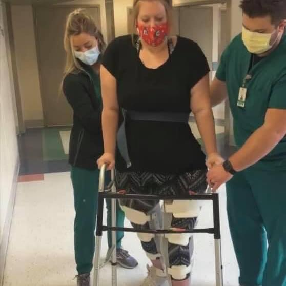 paralyzed woman using walker with support