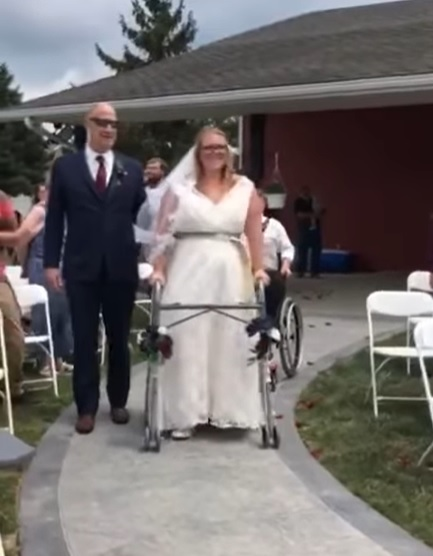 bride using walker to go down the aisle beside her father
