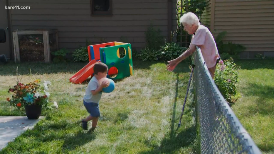 little boy carrying balls over to old woman