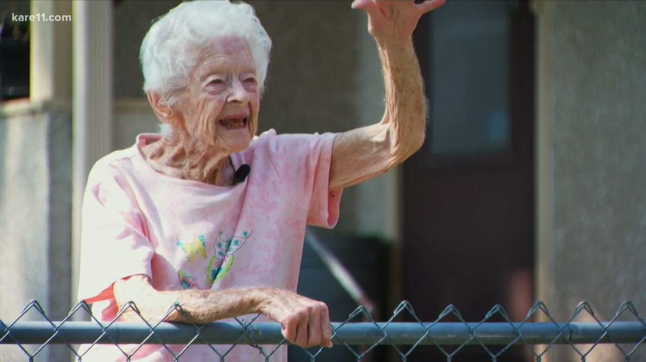 old woman smiling and waving