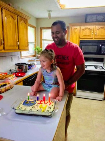 Ivy sitting on a counter near her dad and her fourth birthday cake