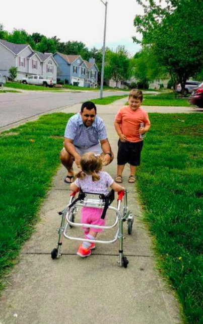 Ivy moving toward her dad and brother in a walker