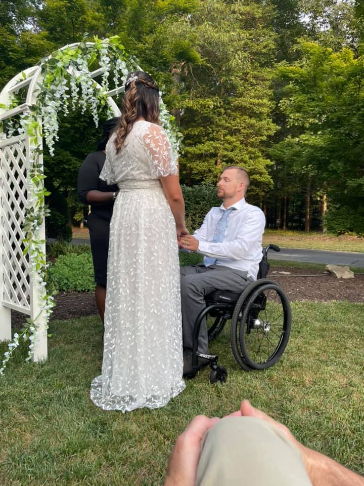 bride holding hands with groom in wheelchair