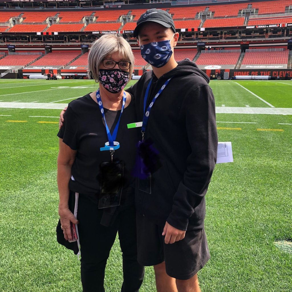 mom and son standing on football field
