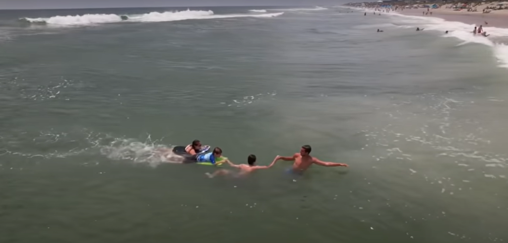 two men pulling mom and son to shore