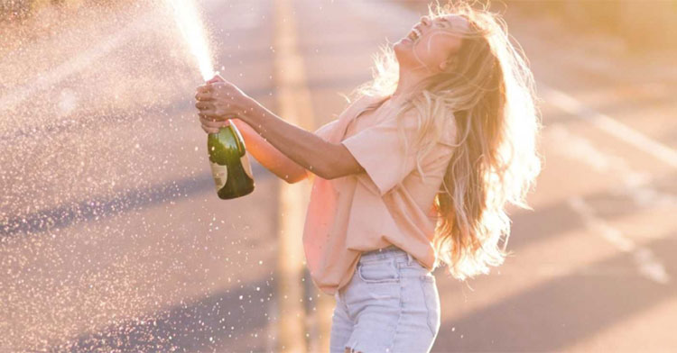smiling woman popping champagne bottle