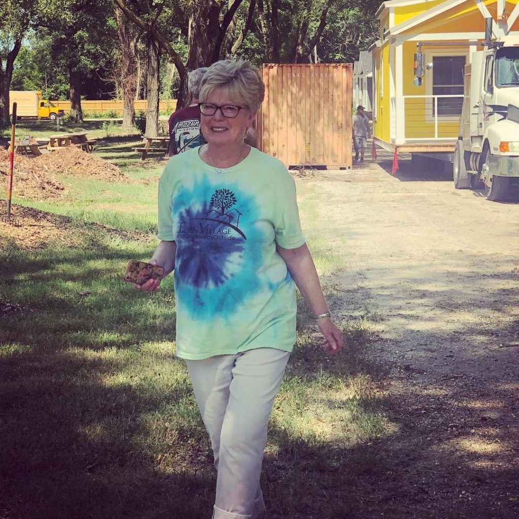 woman in glasses walking with tiny home behind her