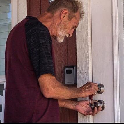 older man unlocking front door