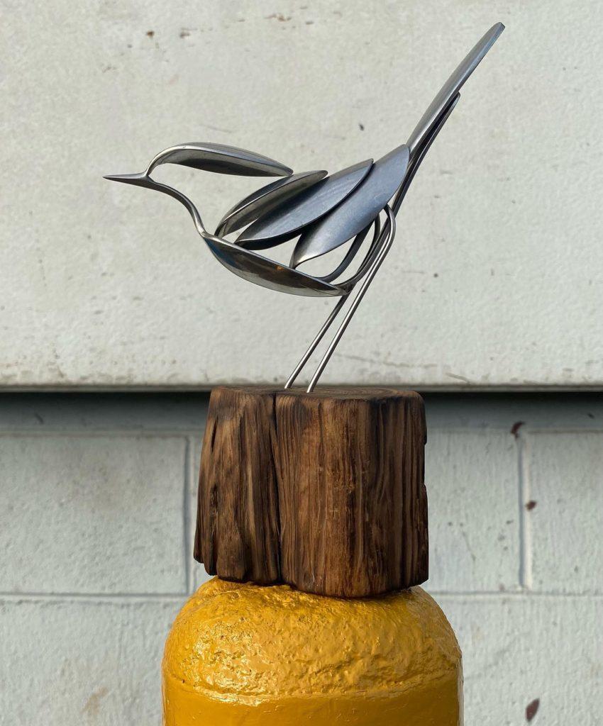 bird sculpture on wooden stand