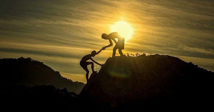one person helping another up a mountain at sunset