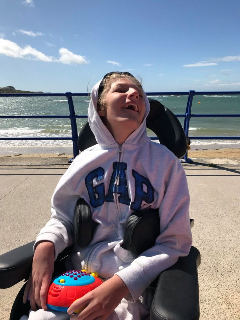 teenage girl in wheel chair smiling and holding ladybug toy