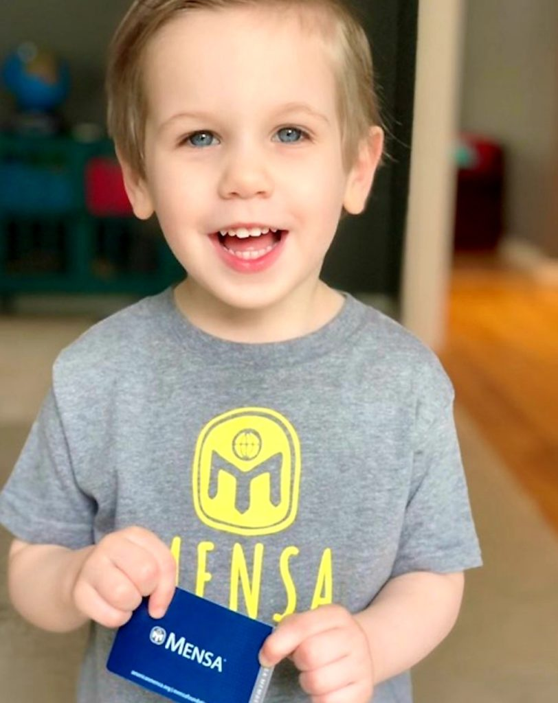 toddler holding mensa card