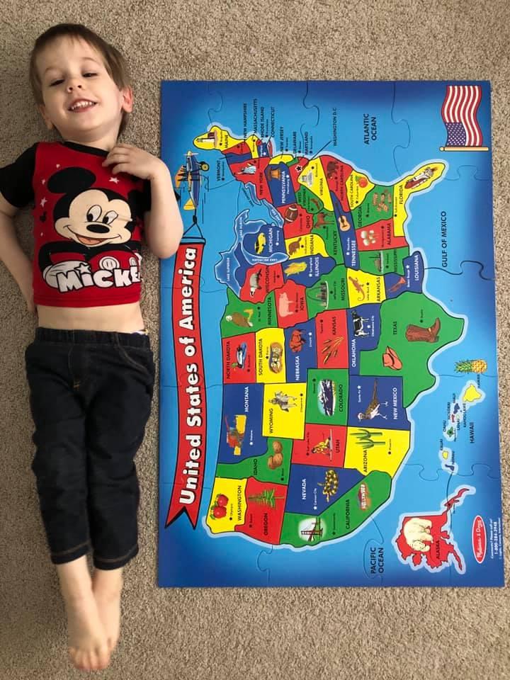 toddler lying on ground next to unites states map