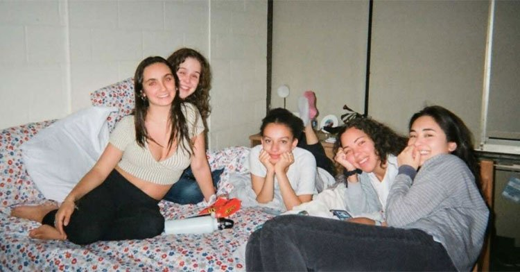 five college students sitting on a bed