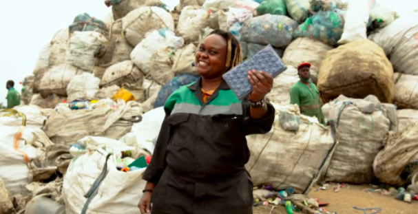 woman holding plastic brick in front of trash bags