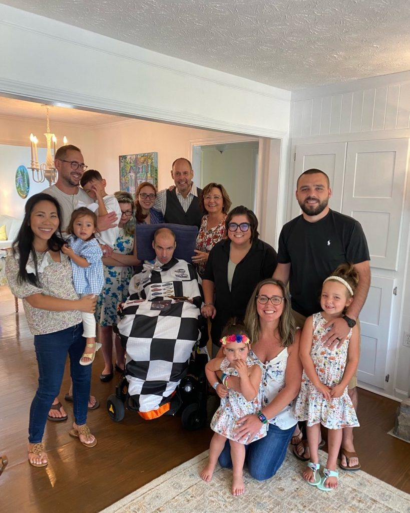 family gathered for a picture around man in wheelchair