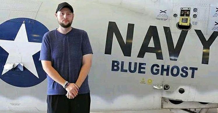 man posing in front of navy plane