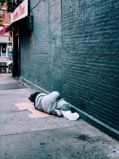 homeless person sleeping next to building