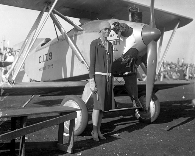 amelia earhart standing in front of airplane